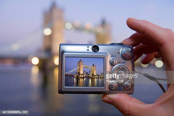 Person taking picture of Tower Bridge at sunrise