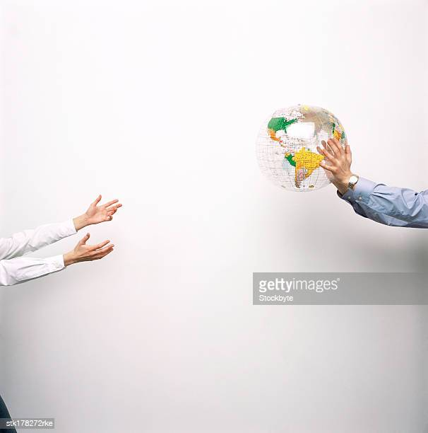 Person throwing a globe to another person