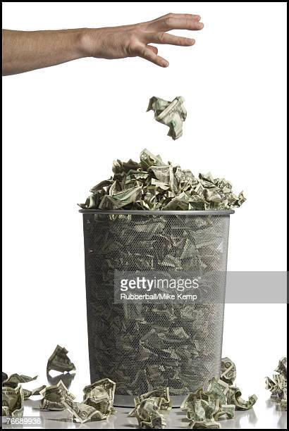 Person throwing crumpled money into waste paper basket