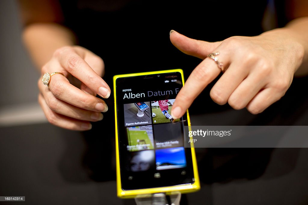 A person touches a Nokia Lumia smartphone during a demonstration at the telecoms stand at the 2013 CeBIT technology trade fair on March 5, 2013 in Hanover, Germany. CeBIT will be open March 5-9.