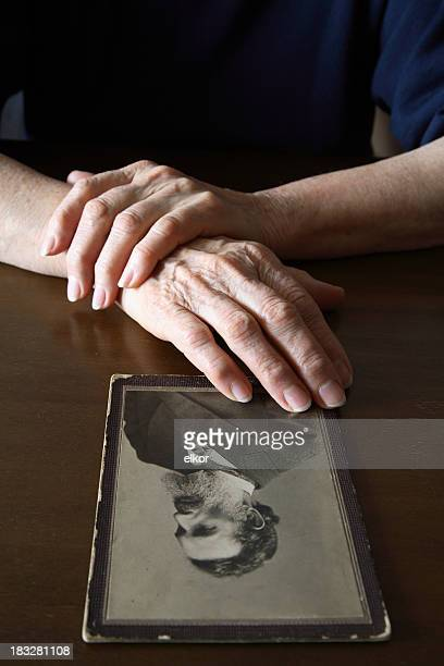 A person touching and viewing an old man portrait on a table