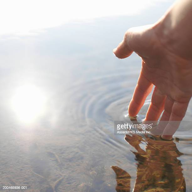 Person touching surface of lake water (focus on hand)