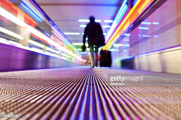 Silhouette d'homme d'affaires voyageant sur l'escalier roulant