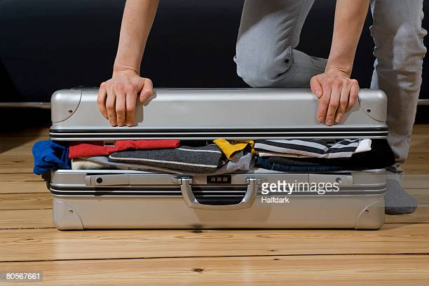 A person trying to close a suitcase
