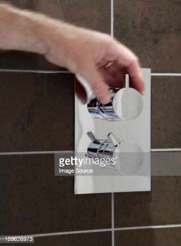 Person turning a knob in the shower