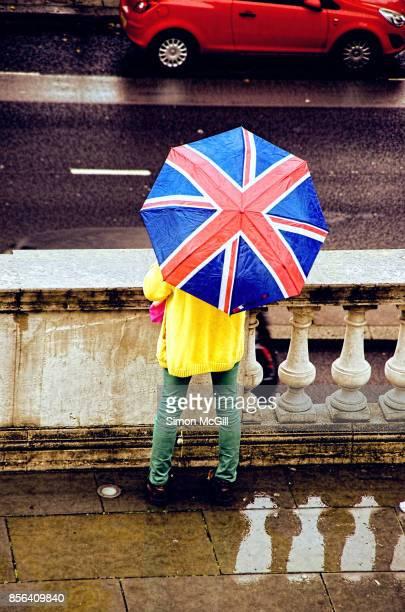 Person under a Union Jack umbrella in London, England, United Kingdom