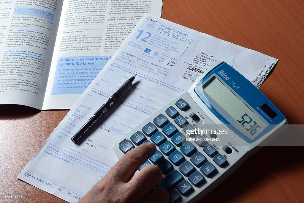 A person uses a calculator as he fills out a prefilled tax declaration for the 2012 income tax on March 31 2013 in Paris AFP PHOTO / MIGUEL MEDINA