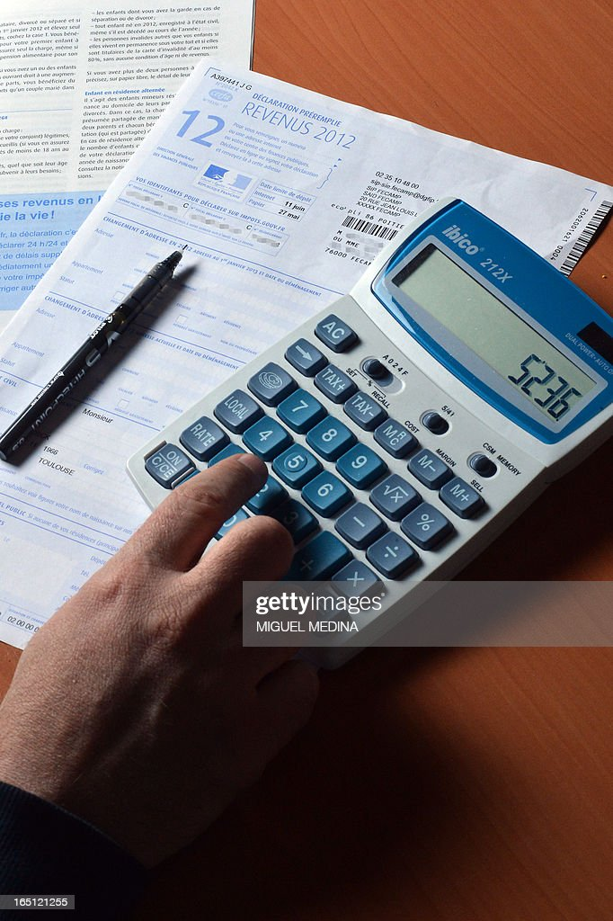 A person uses a calculator as he fills out a pre-filled tax declaration for the 2012 income tax on March 31, 2013 in Paris.