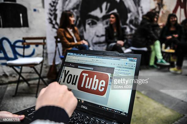A person uses a laptop computer showing Youtube's logo on March 27 2014 in Istanbul near a poster Berkin Elvan the 15yearold boy who died nine months...