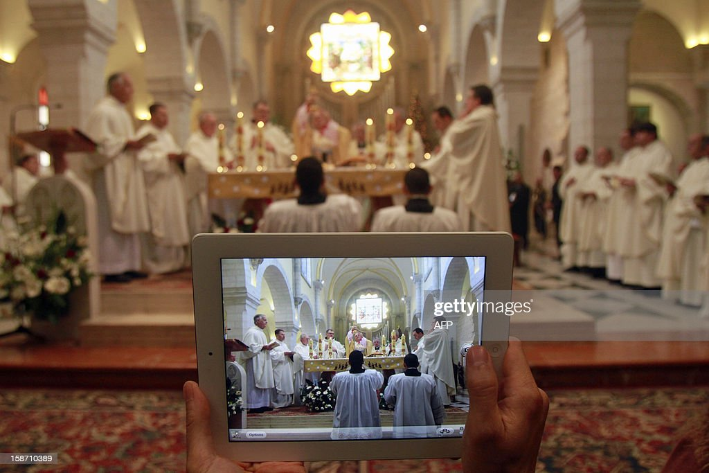 A person uses a tablet computer to take a picture of the Latin Patriarch of Jerusalem Fuad Twal, the head of the Roman Catholic Church in the Holy Land, leading the Christmas morning mass at the Church of the Nativity traditionally believed to be the birthplace of Jesus Christ, in the West Bank town of Bethlehem on December 25, 2012. Thousands of people streamed into the West Bank city of Bethlehem to mark Christmas, as the Latin Patriarch urged 'men of good will' to seek peace in the Middle East. AFP PHOTO/MUSA AL SHAER