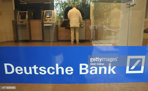 A person uses an automated banking machine at a branch of German bank Deutsche Bank on April 27 2015 in Berlin Germany Deutsche Bank announced...