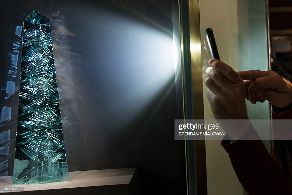 A person uses an iPhone to photograph the Dom Pedro after its unveiling in the Janet Annenberg Hooker Hall of Geology, Gems and Minerals at the Smithsonian's National Museum of Natural History December 6, 2012 in Washington, DC. The Dom Pedro aquamarine, currently considered the largest single piece of cut gem aquamarine in the world, was donated to the Smithsonian by Jane Mitchell and her husband Jeffrey Bland. AFP PHOTO/Brendan SMIALOWSKI