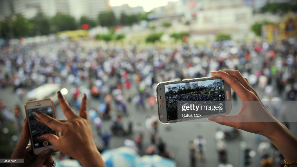A person uses smartphones to capture protesters marching through the city centre during an anti-coup rallly on May 25, 2014 in Bangkok, Thailand. Protesters marched through central Bangkok, defying a martial law decree that prohibits public assembly. The Thai armed forces seized power in the May 22 coup after months of street protests and political unrest.
