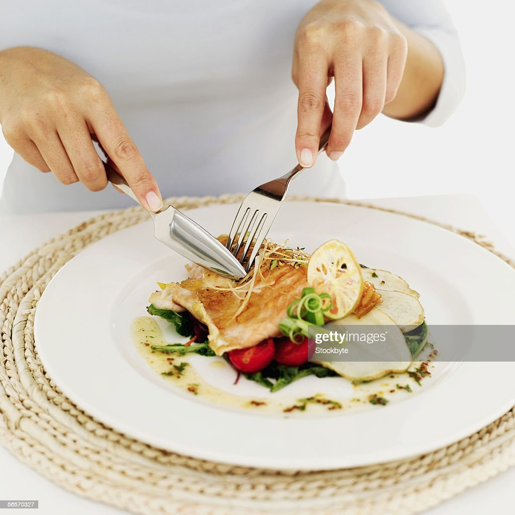 person using a fork and knife on a plate of grilled salmon : Stock Photo