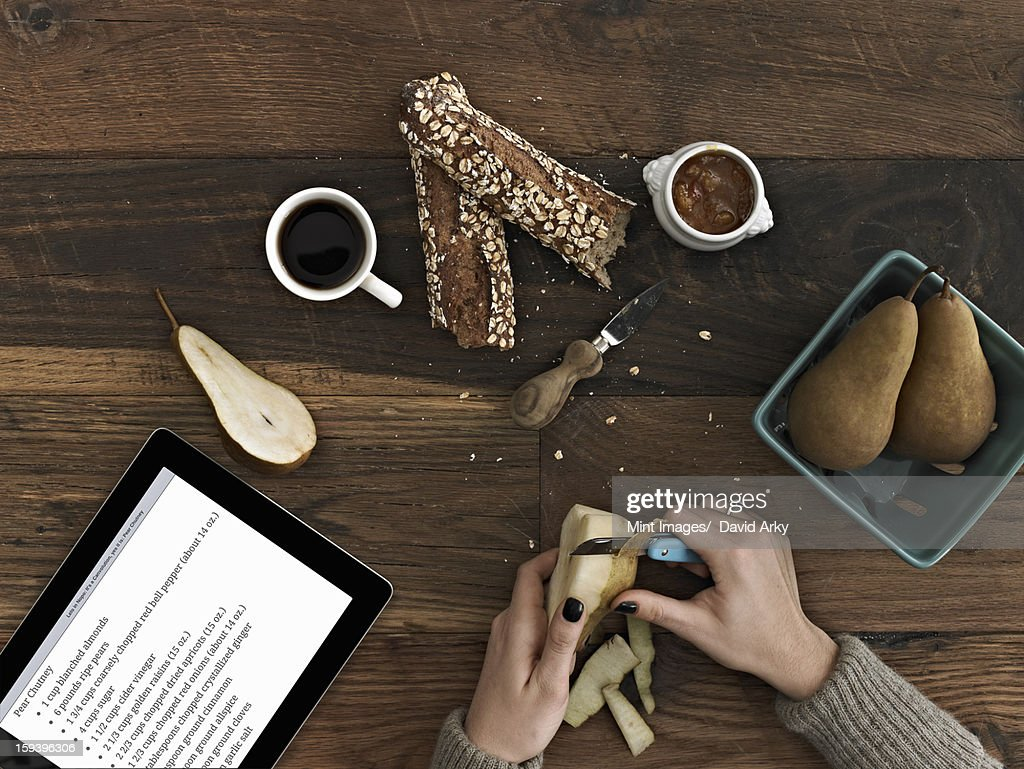 A person using a peeling knife to peel a pear. A computer tablet device with the screen displaying instructions, a recipe.