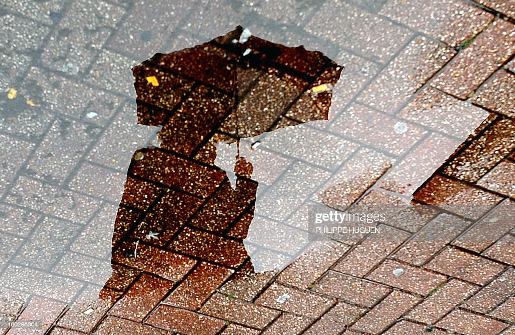 A person using an umbrella to shelter themselves from the rain is reflected in a puddle on September 11, 2013, in Lille.