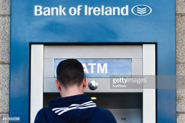 A person using Bank of Ireland cash maschine in Dublin's city center On Friday March 24 in Dublin Ireland