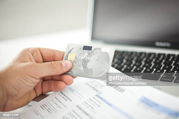 Person using credit card and laptop computer
