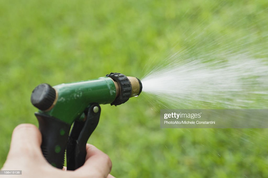 Person using spray nozzle on garden hose to water lawn, cropped