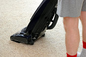 Lower half of a man wearing shorts vacuuming a tan rug with an upright vacuum as part of his housecleaning chores..
