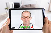 Close-up Of A Person Video Conferencing With Happy Male Doctor On Digital Tablet