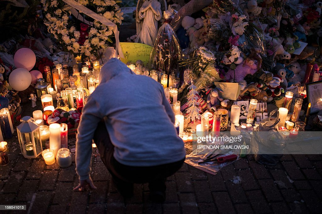A person visits a makeshift memorial on December 18, 2012 in Newtown, Connecticut. Students in Newtown, excluding Sandy Hook Elementary School, returned to school for the first time since last Friday's shooting at Sandy Hook which took the live of 20 students and 6 adults. AFP PHOTO/Brendan SMIALOWSKI