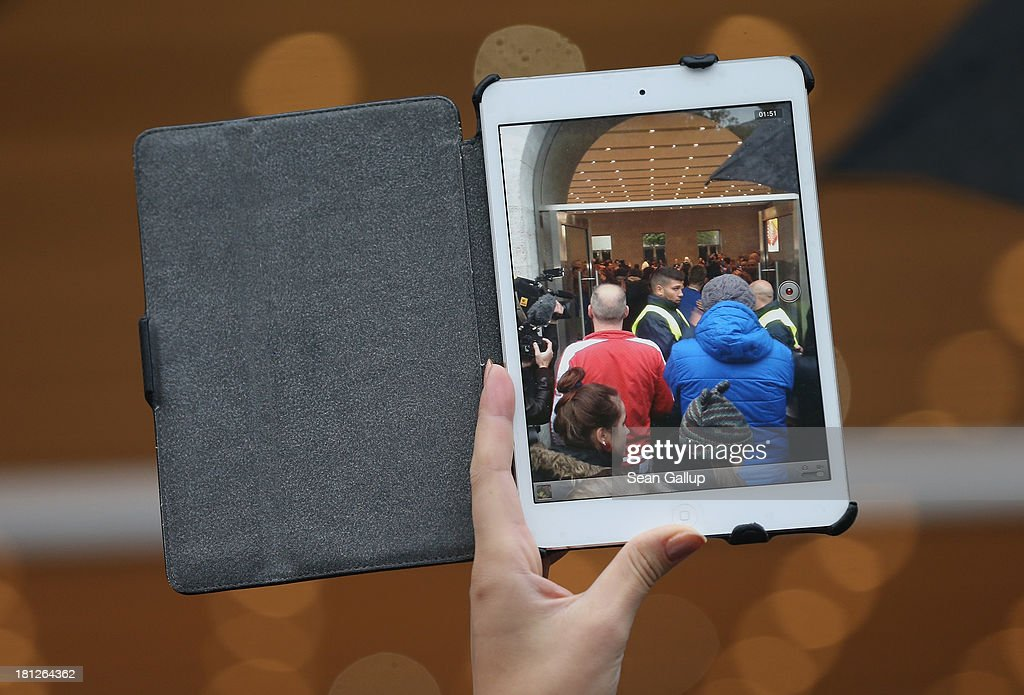 A person waiting outside the Berlin Apple Store films with an apple iPad Mini into the store on the first day of sales of the new Apple iPhone 5S and 5C smartphones on September 20, 2013 in Berlin, Germany. The new iPhone 5S and 5C phones went on sale all over the world today and hundreds of customers waited outside the Berlin store in the rain to be among the first to buy the new phones starting at 8am.