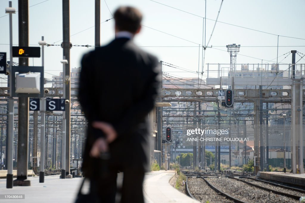 A person waits for a train at the Saint Charles train station during a strike by French SNCF railway company employees on June 13, 2013, in Marseille. The strike was called by unions hostile to reforms of the train services sector recently proposed by the French government on May 29.