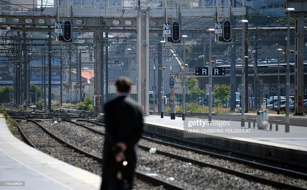A person waits for a train at the Saint Charles train station during a strike by French SNCF railway company employees on June 13, 2013, in Marseille. The strike was called by unions hostile to reforms of the train services sector recently proposed by the French government on May 29. AFP PHOTO / ANNE-CHRISTINE POUJOULAT