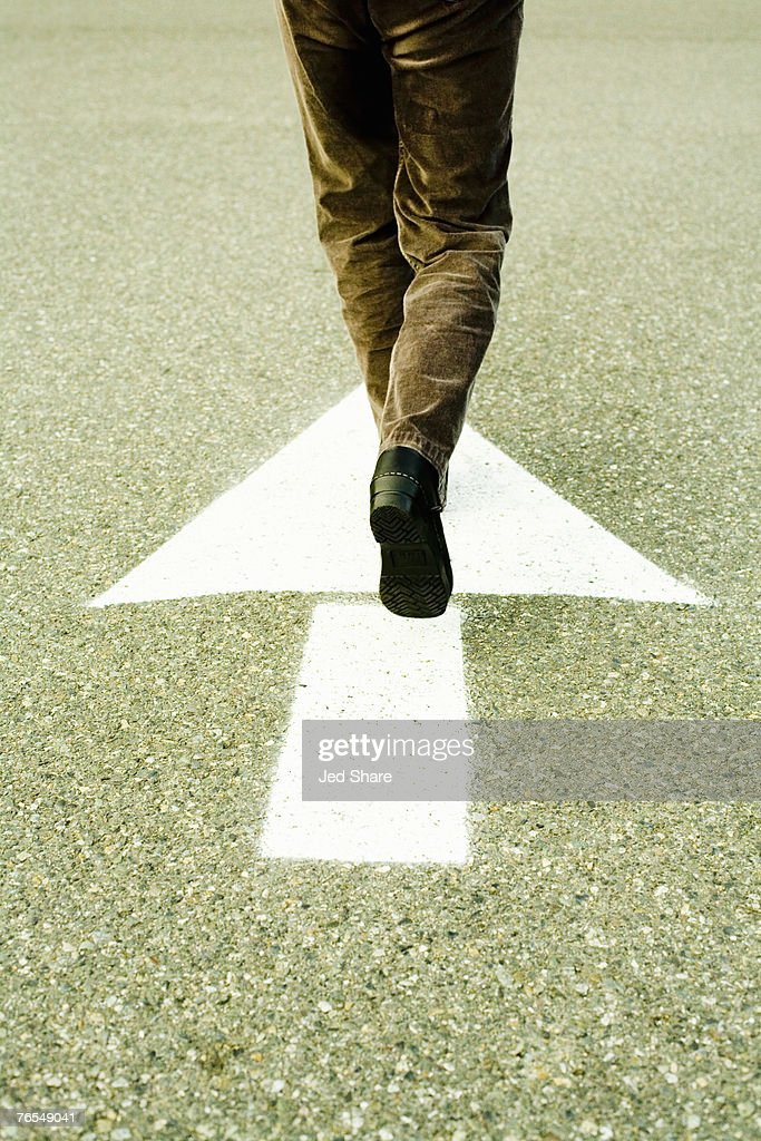 Person walking in direction of arrow on road : Stock Photo