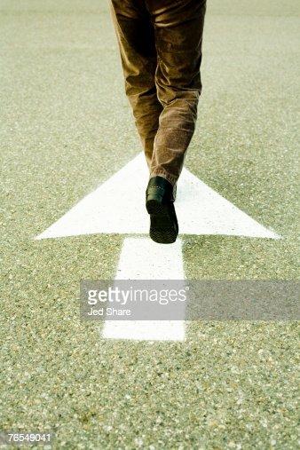 Person walking in direction of arrow on road : Bildbanksbilder