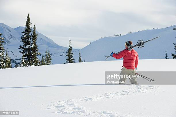 Person walking in knee-deep snow with skis on shoulder