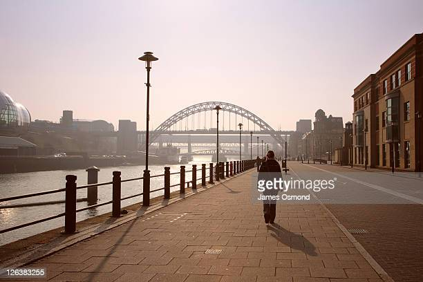 A person walking next to the Quayside approaching the Tyne Bridge in Newcastle Upon Tyne.