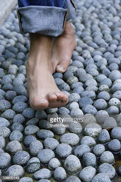 Person walking on pebbles and receiving foot massage