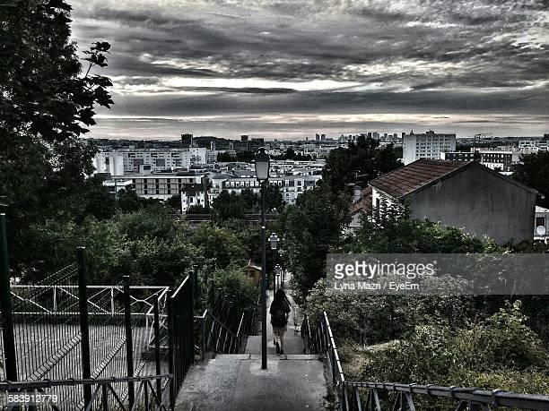 Person Walking On Staircase By City Against Sky At Dusk