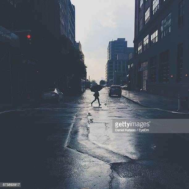 Person Walking On Wet Street With Umbrella At Monsoon