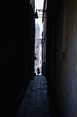 Person walking out of dark alley, Venice, Italy