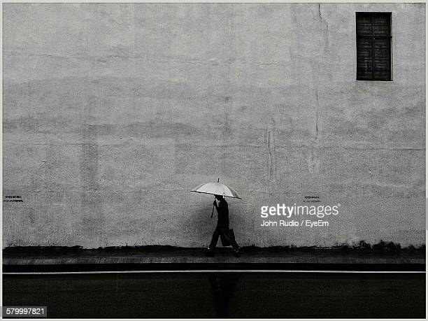 Person Walking With Umbrella On Footpath Against Wall