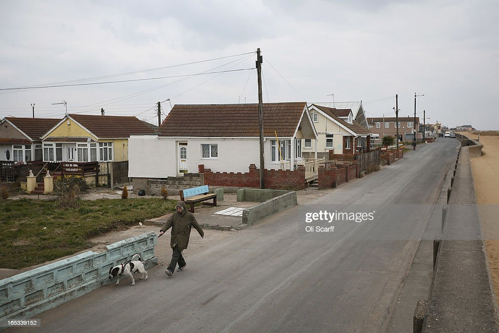 A person walks a dog near dilapidated properties stand in the seaside town of East Jaywick, the most deprived place in England, on April 3, 2013 in Jaywick, England. The Government's 2011 Indices of Multiple Deprivation' measure ranks Jaywick as the most deprived of all 32,482 small wards in England and Wales. The area also has the greatest number of young people not in employment, education or training; one third of 16 to 24 year-olds claim Jobseeker's Allowance, compared to the national average of 6 per cent. Changes to the benefits and tax system which came into force on April 1, 2013 have included a cut in housing benefit payments for working-age social housing tenants whose property is deemed larger than they need and council tax support payments now being administered locally.