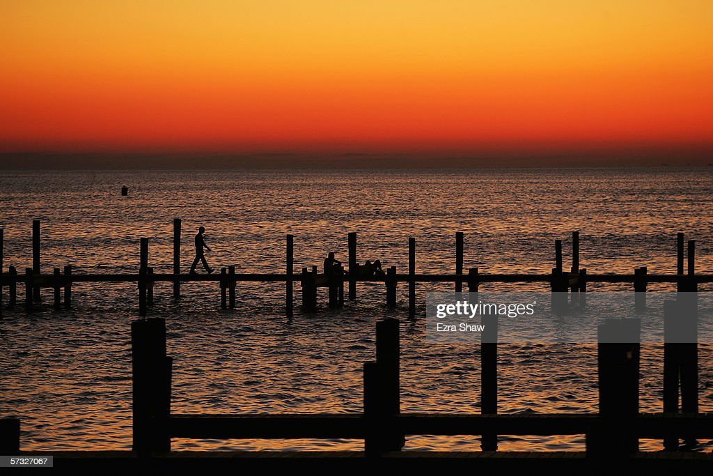 A person walks along the dock as the sun begins to rise at Ocean Beach on September 2 2005 on the Fire Island Ferry off the coast of Long Island in...