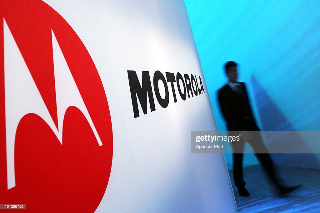 A person walks by a Motorola sign at the launch of three new Motorola smartphones under its Razr brand that will become available for Verizon customers on September 5, 2012 in New York City. The new phones, the Droid Razr HD, the Razr M and the Razr Maxx HD, will all use Google's Android operating system. Motorola Mobility was acquired by Google in August of 2011.