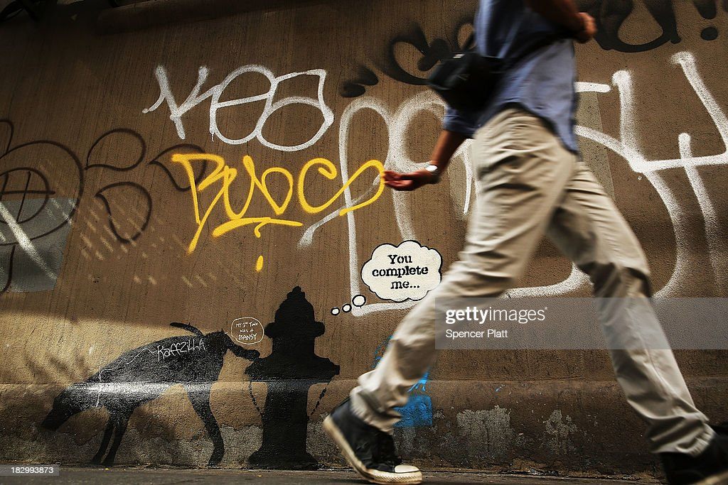 A person walks by a new Bansky work on a side of a wall on October 3, 2013 in New York City. New work by the mysterious British street artist Banksy has appeared in New York after he announed a a month-long residency in the city. Three works in total have appeared in recent days with two of them quickly being vandalized by other graffiti.