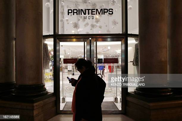 A person walks by an entrance of the Printemps department store after an armed robbery in its jewelery stand on February 19 2013 in Paris The 2...
