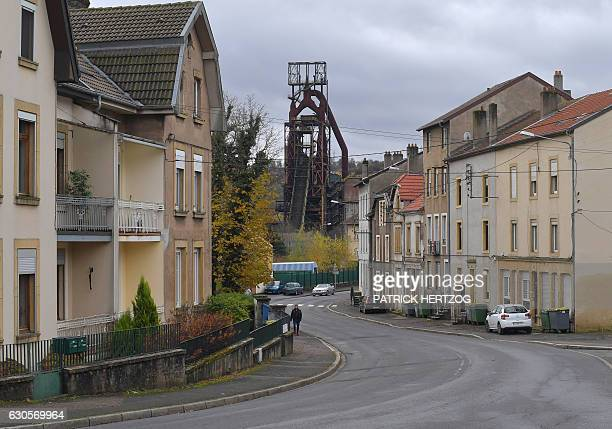 A person walks in a street on November 17 2016 near the blast furnaces of the steel plant in Hayange eastern France / AFP / PATRICK HERTZOG