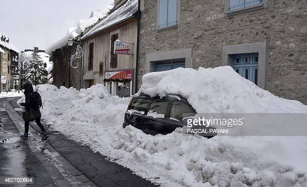 A person walks near a car covered by snow on February 3 2015 near SaintLarySoulan southern France French authorities have forbidden the traffic on...