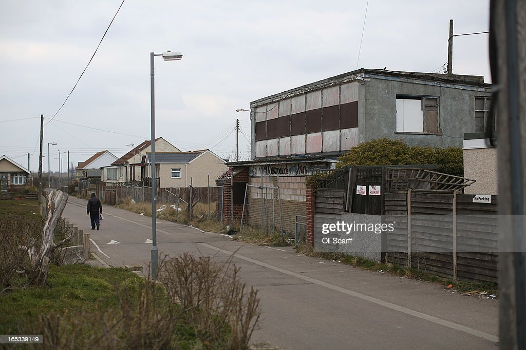 A person walks near dilapidated properties stand in the seaside town of East Jaywick, the most deprived place in England, on April 3, 2013 in Jaywick, England. The Government's 2011 Indices of Multiple Deprivation' measure ranks Jaywick as the most deprived of all 32,482 small wards in England and Wales. The area also has the greatest number of young people not in employment, education or training; one third of 16 to 24 year-olds claim Jobseeker's Allowance, compared to the national average of 6 per cent. Changes to the benefits and tax system which came into force on April 1, 2013 have included a cut in housing benefit payments for working-age social housing tenants whose property is deemed larger than they need and council tax support payments now being administered locally.
