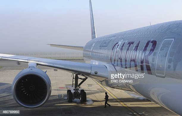 A person walks near one of the two Airbus A350900 aircrafts for the Qatar Airways company on December 22 2014 at the Airbus Group center in Toulouse...