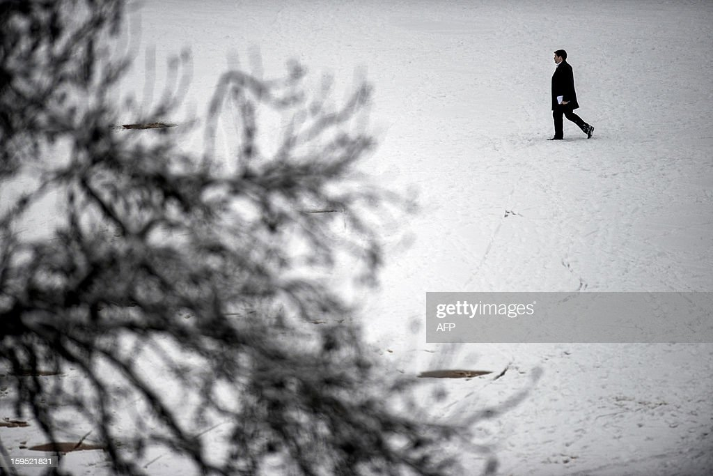 A person walks on a snow covered street, on January 15, 2013, in a street of Lyon, central eastern France, after snow blanketed several French departments.