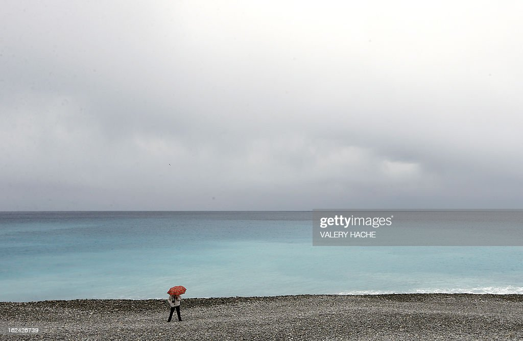 A person walks on the beach along the Mediterranean sea on February 23, 2013 in the southeastern French city of Nice.