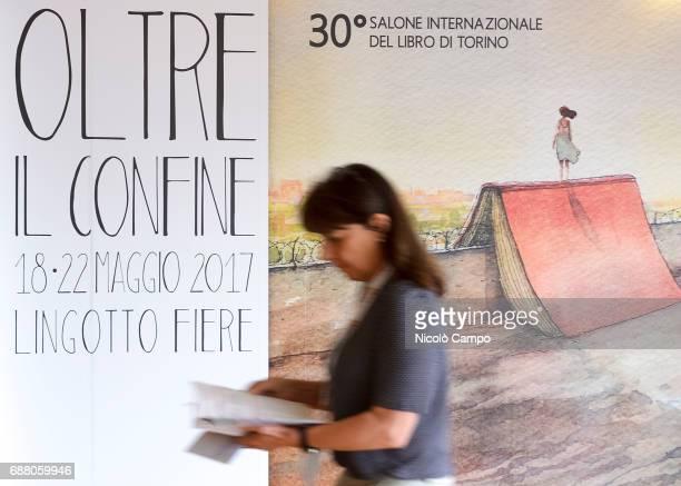 A person walks past a billboard of the 30th Turin International Book Fair